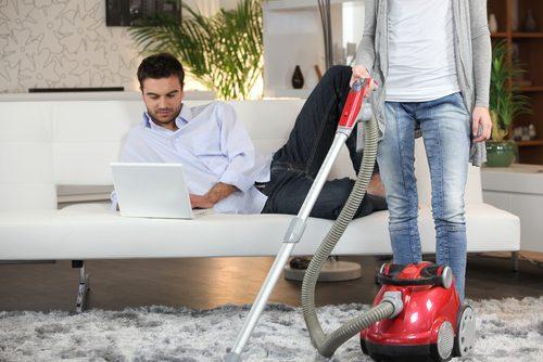 女性が掃除中にパソコンを見る男性