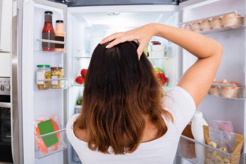 冷蔵庫の中を見つめる女性
