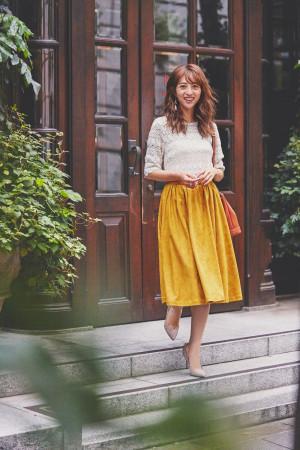 上品なスウェード素材のイエロースカートが主役のレディスタイル