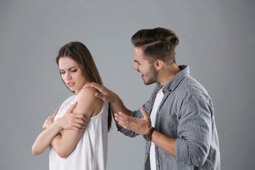 肩に手を置く男性を嫌がる女性