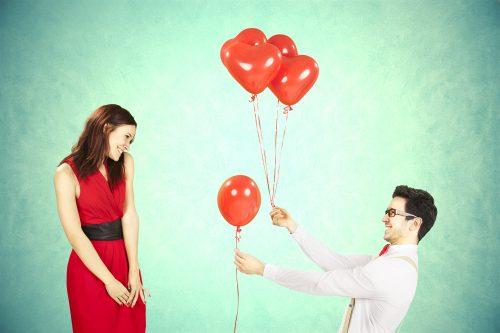 風船を持って女性にアプローチする男性