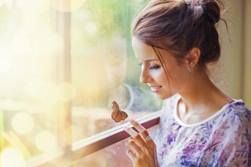 窓の近くで蝶に触れる女性