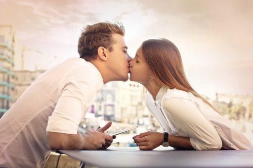 テーブルを挟んでキスする男女