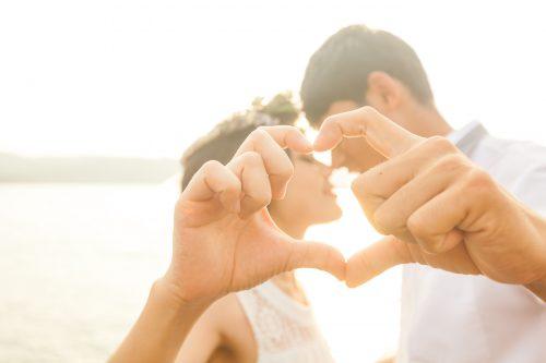 指でハートを作りながらキスをするカップル
