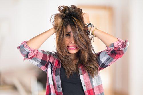 頭を抱え髪をふりみだす女性