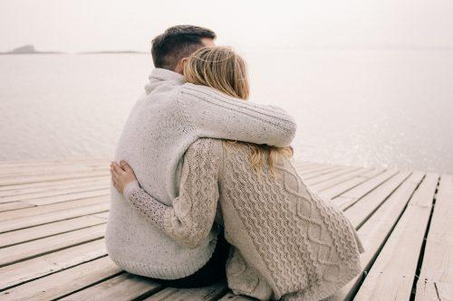 海の近くで抱きしめ合うカップル