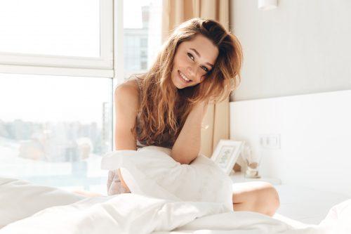 ベッドで笑う女性