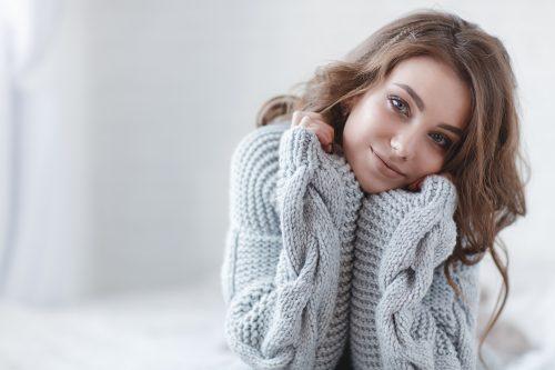 セーターを着て首をかしげる女性