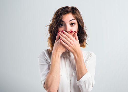 口元を手で覆う女性