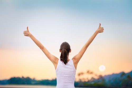 空に向かって指を立てる女性