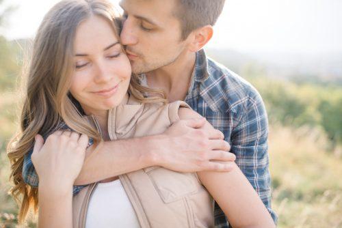 女性のこめかみにキスする男性