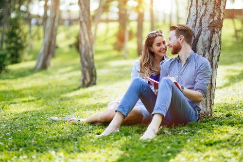 公園で芝生に座るカップル