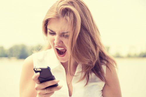 スマホを見て怒る女性