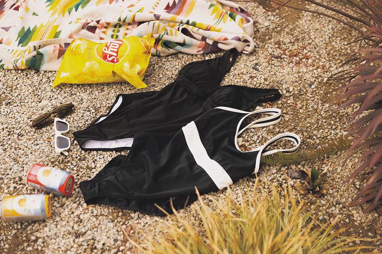 (上)黒のワンピース型水着。(下)黒のワンピース型水着。胸下に白いラインが太く、横に入っている。肩紐部分は白と黒の混合。