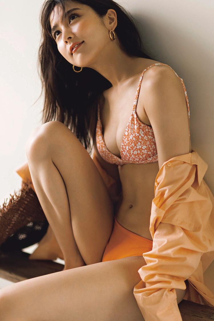 上はオレンジベースに小花柄が描かれており、下はシンプルなオレンジのビキニ。柔らかいオレンジ色のシャツを着崩している。耳には大きなフープ型のピアス。また、座っていて目線を上にあげているポージング。