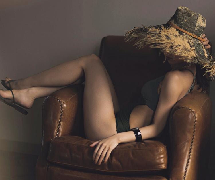 カーキのモノキニビキニを着た石川恋(専属モデル)がソファに座っているのを、左側から撮影した画像。