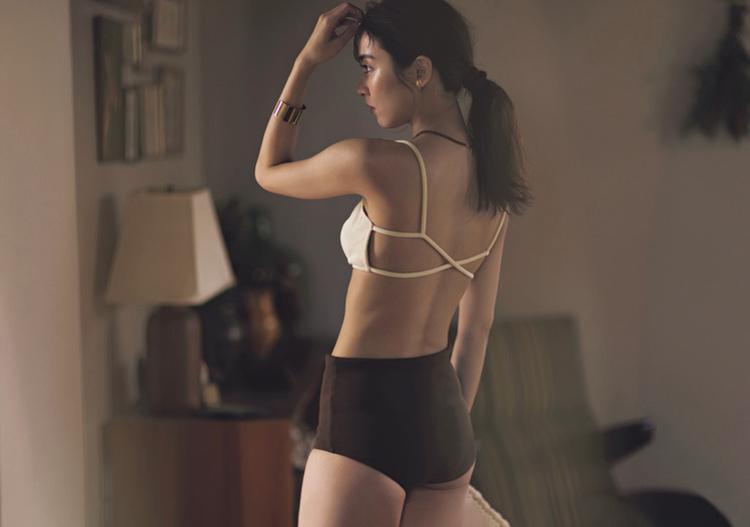 アイボリーの水着を着用した石川恋を、ななめ後ろから撮影した画像。水着の下はブラウンに近い色。