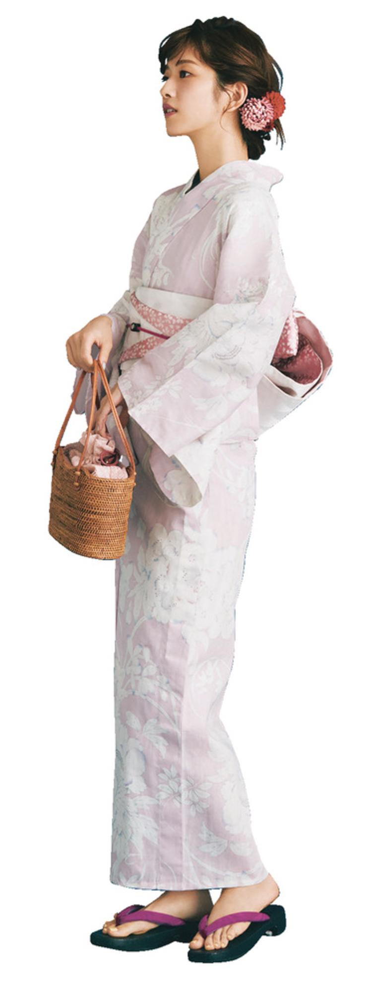 淡いピンク地に、いろい派ながらが繊細に描かれている浴衣を着用したモデルを、左側から撮影した写真。手にはかごバッグを持っており、草履の鼻緒は紫色。また、ピンクと赤の花の髪飾りをしている。
