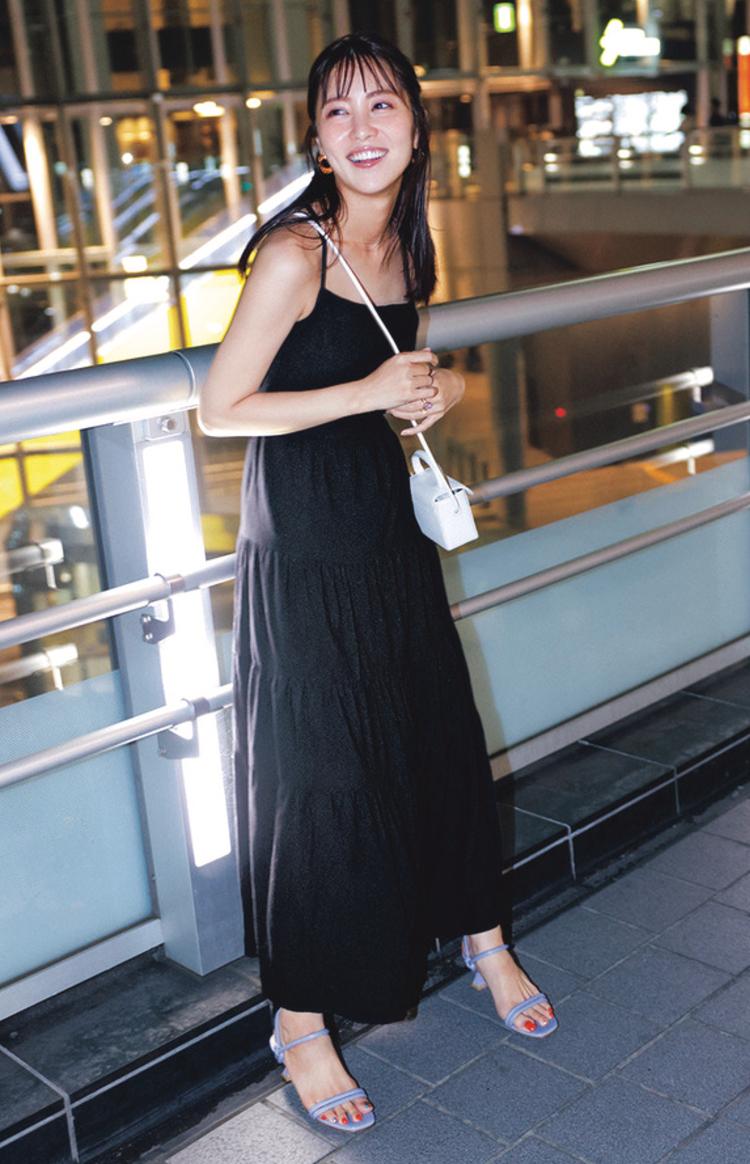 黒のキャミソールワンピース。白いショルダーバッグと水色のサンダルを着用している。
