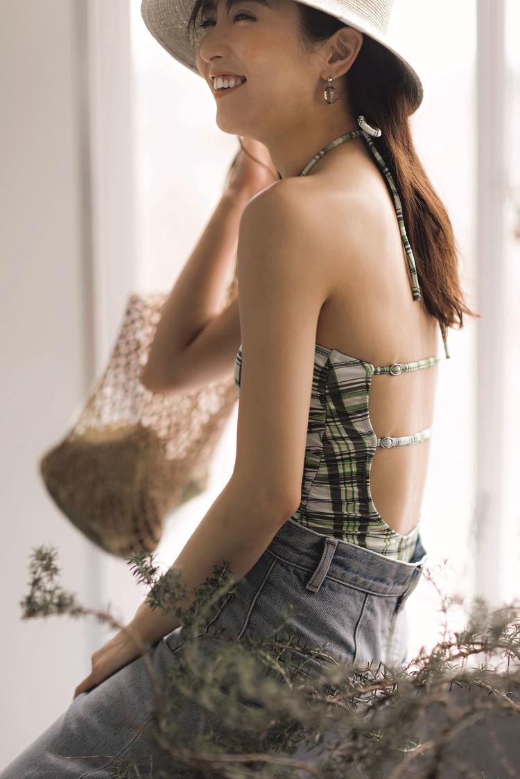 緑のチェック水着に、ジーンズを合わせたコーディネート。モデルを左側から撮影した写真。