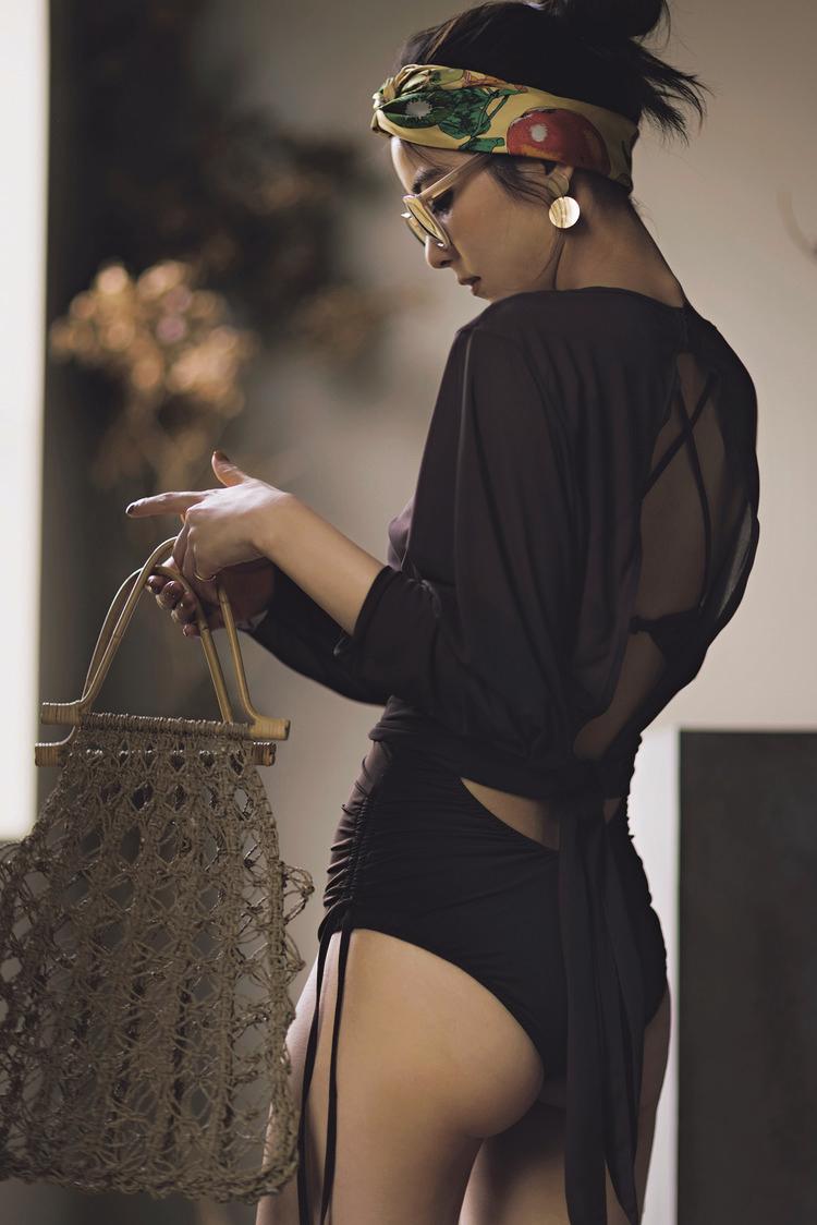 ブラウンのラッシュガードつき水着に、サングラス、満月のように丸くて大きいイヤリング、バンダナ、あみバッグを身につけている。