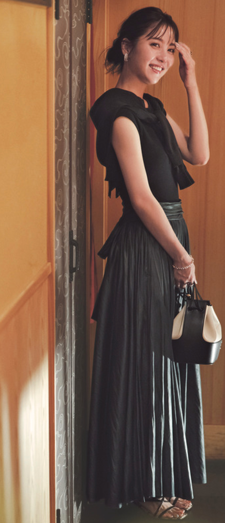深いグリーンのロングスカートに、黒のノースリーブトップス、カーディガンを組み合わせている。手には黒と白のバッグ。