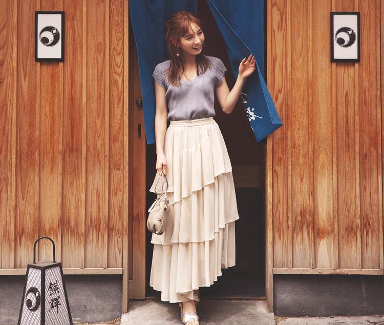 白のロングスカートに、淡いブルーのトップスを組み合わせたコーディネート。靴はシルバーのサンダル、バッグは小さめでベージュカラー。