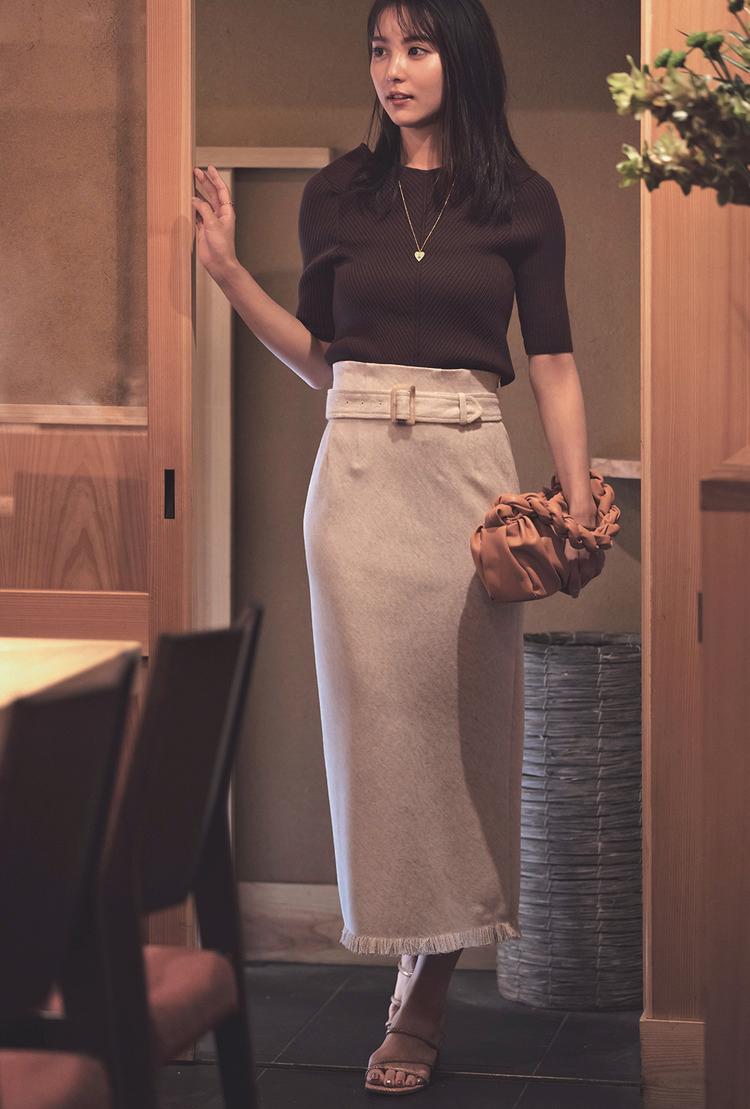 ブラウンのトップスに、淡いピンクのロングスカートを組み合わせ。ロングネックレスと、ベージュとオレンジが混ざったような色のバッグをセカンドバッグのように持っている。