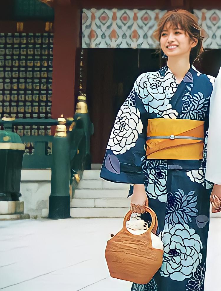 上品なネイビーと爽やかブルーの色合わせが特徴的な、大花柄の浴衣。帯はオレンジ、手には大き目のかごバッグを持っている。