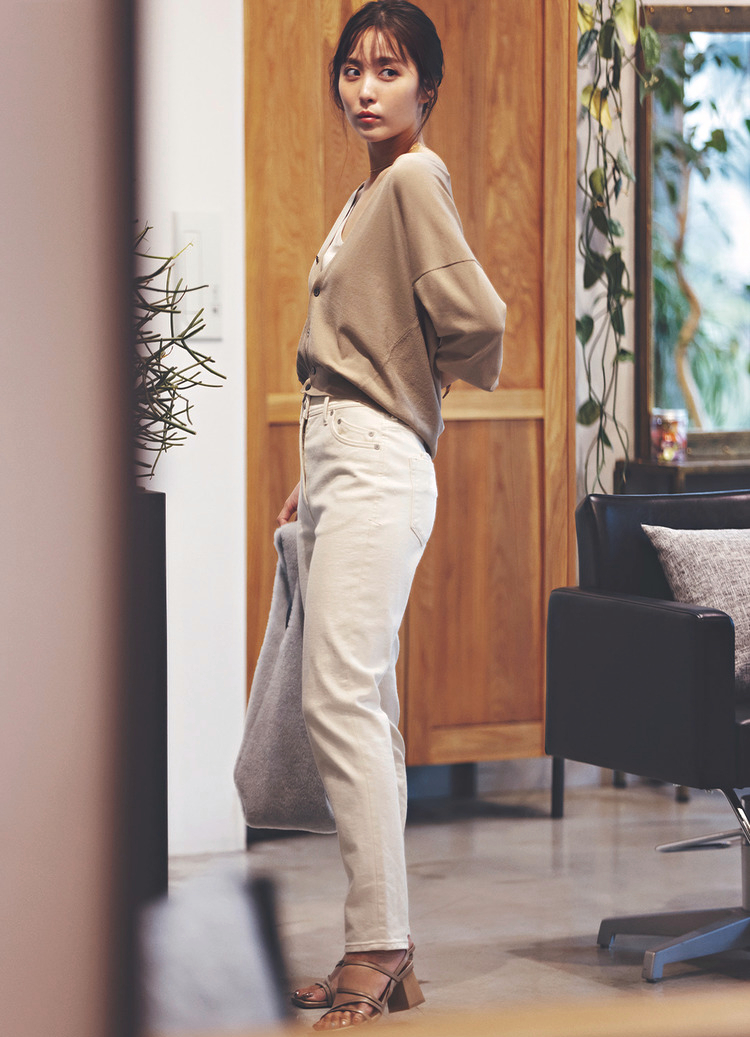 ミルクティーベージュのニットに、エクリュデニム、ベージュのサンダルを合わせたスタイル。手に持っている大きめのバッグはグレー。