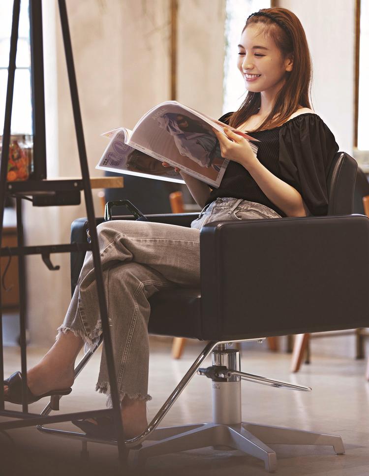 美容院の椅子に座っている写真。黒いニットにジーンズを合わせたスタイル。黒いサンダルを着用している。