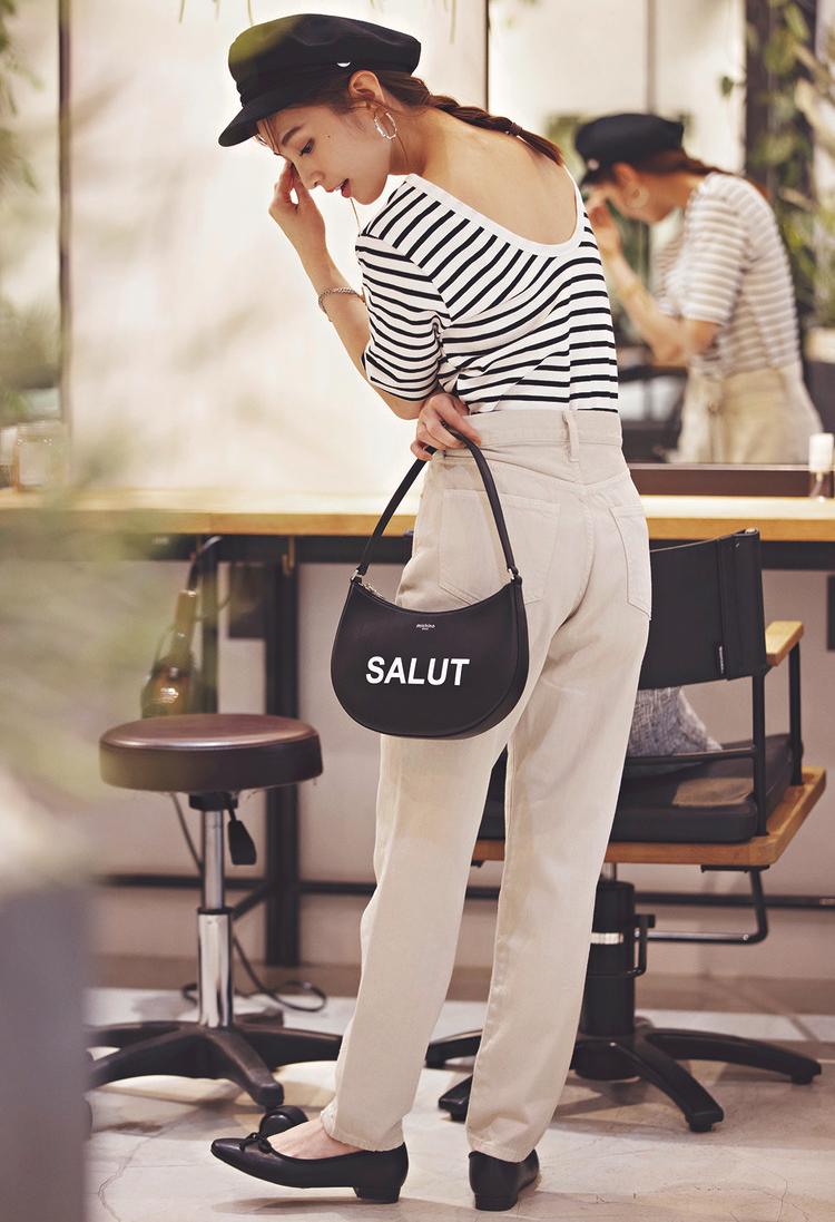 ボーダーシャツに白パンツを合わせたスタイル。靴、帽子、バッグは黒で揃えている。