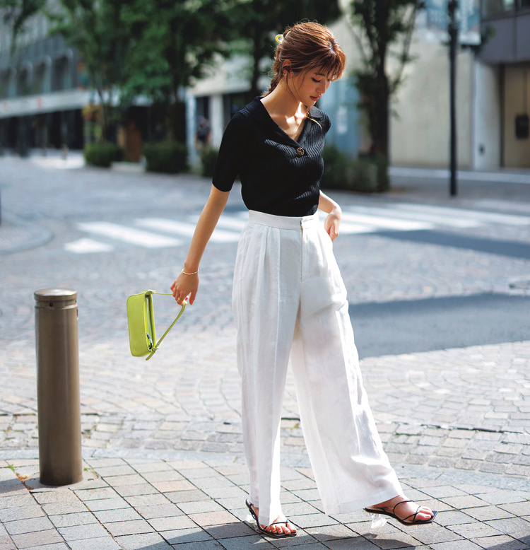 ②のポロニットに、白いワイドパンツ、黄緑色のミニバッグを使用したコーディネート。靴はブラックで、ヒール部分はクリアになっている。