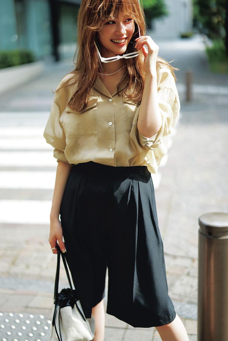 濃いクリーム色のシャツに、④のハーフパンツを合わせたコーディネート。白いサングラスと白×黒のバッグも使用している。
