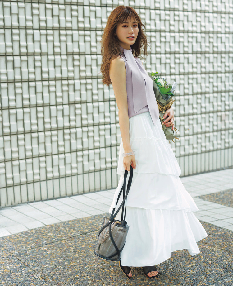 ①のニットと③のスカートを合わせたコーディネート。サンダルは黒、バッグは黒を基調とした透けるデザインで、手首にはクリアのバングルをつけ、花を持っている。